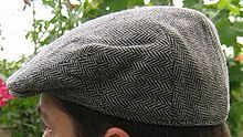 A flat cap, also known as a longshoreman's cap, scally cap, Wigens cap, ivy cap, golf cap, driving cap, Jeff cap, or in Scotland, bunnet, or in Wales, Dai cap, or in New Zealand, cheese-cutter, is a rounded men's or women's cap with a small stiff brim in front. Cloths used to make the cap include wool, tweed (most common), and cotton. Less common materials may include leather, linen or corduroy.