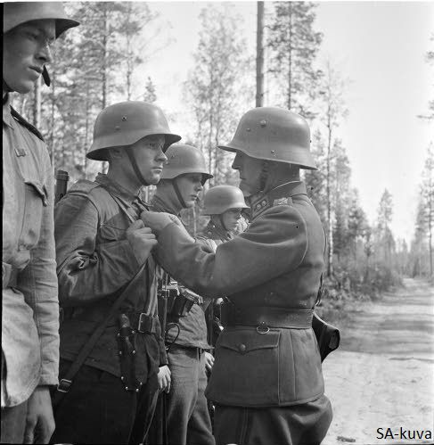 Officer (Lieutenant colonel) decorating soldiers who showed a great bravery during capturing the Ristinsalmi. Ilomantsi and Tolvajärvi 1941.08.08
