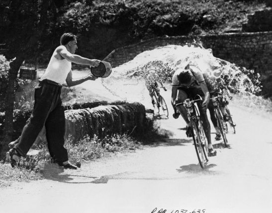 A spectator helps Jan Nolten to cool off during stage 14, 1953