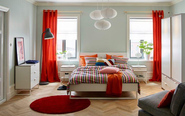 Quarto amplo com uma cama grande de casal com roupa de cama em laranja, vermelho, verde, rosa e branco Combinado com mesas de cabeceira, cómodas e um roupeiro, tudo em branco com rebordos em cinzento claro