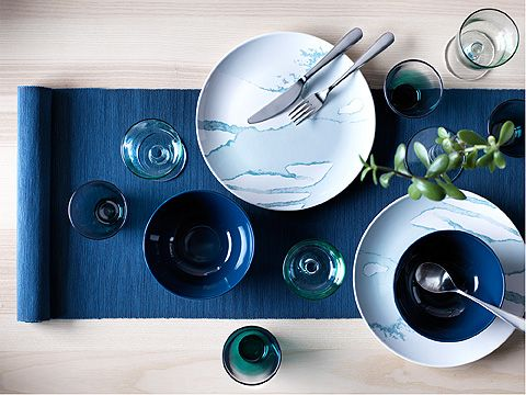 Two blue-grey plates, wine glasses and cutlery on a blue table-runner.