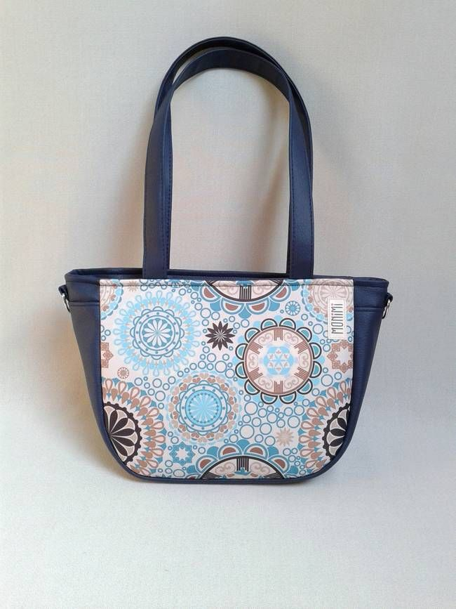 A nagyon kedvelt kék mandala minta most nyárias, könnyed stílusban jelenik meg ezen a táskán. A minta különleges nyomtatási technológiával került az anyagra, UV és időjárás álló, vízhatlan, egyszerűen nedves szivaccsal letörölhető. #City-#bag 37 #női #táska