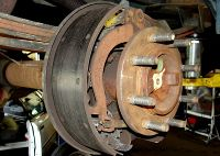 This is a typical rear drum brake setup. The brake shoes are held on with a hardware kit with springs, brake shoe adjuster, parking brake lever and parking brake cable.