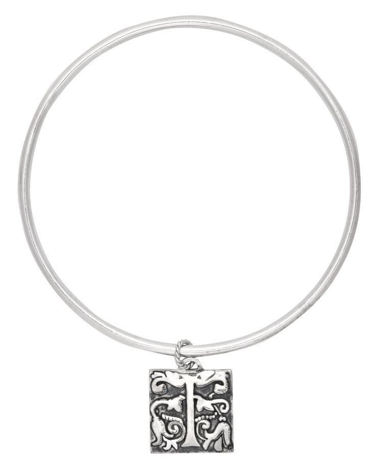 A sterling silver round wire bangle with a square charm that boasts an ornate typography pattern. This unusual detail is the perfect balance between classic and contemporary. The raised pattern is a lustrous gold and is attached to the bangle with a twisted wire jump ring creating a very unusual feature.  Square charm 17mm x 17mm