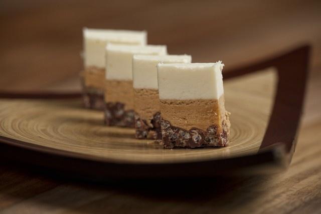 1. Rozpusťte čokoládu s máslem a smíchejte s rýžovými burizony a nutellou. Pak hmotu nalijte do nádoby s rovným dnem, ideálně o rozměrech 20 x 40 centimetrů, aby vznikla vrstva vysoká 1 centimetr. Vložte na 20 minut do mrazáku.2. Rozpusťte máslo s pralinkovou pastou, ušlehejte šlehačku a smíchejte. Vyjměte nádobu z mrazáku a na první vrstvu naneste další vrstvu vysokou 1 centimetr, tentokrát šlehačkovo-pralinkovou. Následně znovu nechte zmrazit dalších 20 minut.3. Rozpusťte máslo s bílou ...