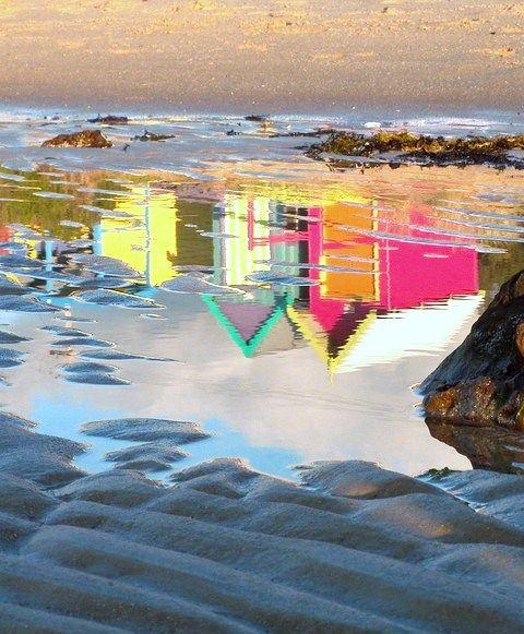 reflets de cabines de plages colorées dans l'eau de mer