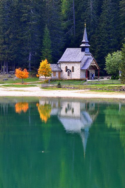 Beautiful reflection of the little white chapel by the lake in Dolomiti, Italy