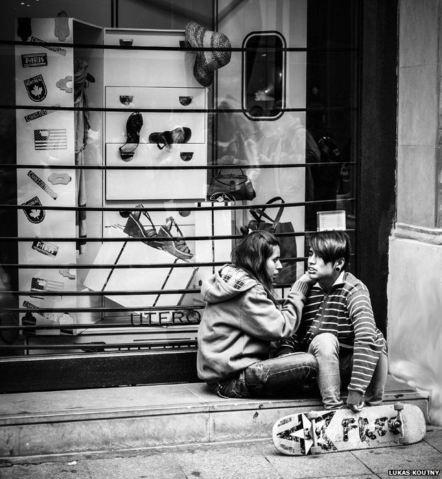 A couple sits on a step in front of a shop