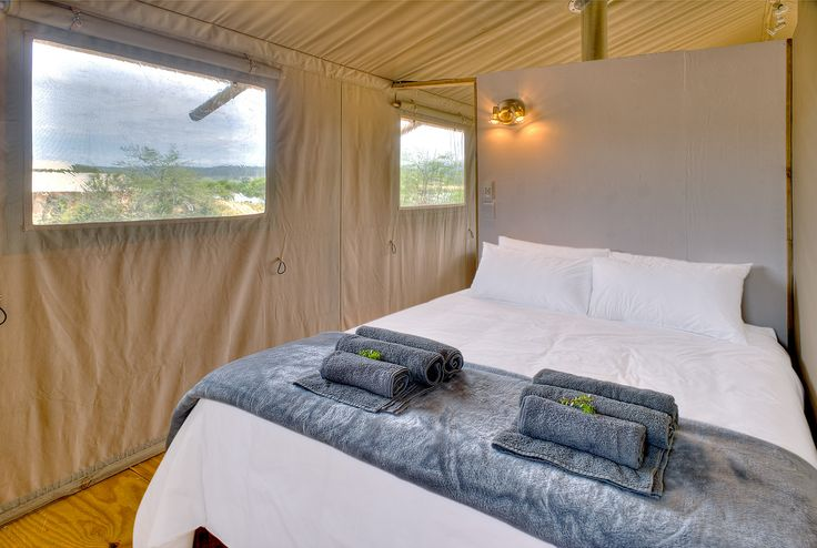 AfriCamps Glamping at Klein Karoo, South Africa. Queen sized extra length bed in the main room of AfriCamps Glamping tent.