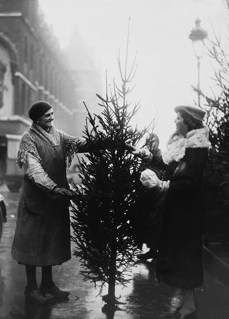 Wonder if this woman, purchasing a Christmas tree in 1933, brought it home on the metro. | 13 Magical Vintage Photos Of Paris At Christmastime