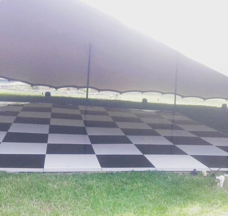 Painted black and white check floor under a marquee installed straight onto grass. Our floors are robust enough to support great weight, and strong enough to create a solid floor even on an uneven surface #connectafloorcape #eventflooringcapetown