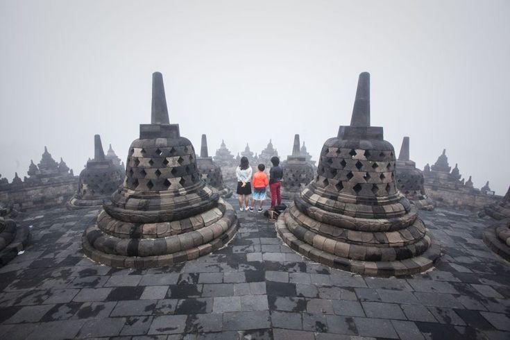"""Cada año, a finales de primavera, cuando la luna llena se alinea con la constelación de Tauro, millones de budistas en todo el mundo celebran la fiesta del Vesak, que conmemora el nacimiento, iluminación y muerte de Siddharta Gautama, Buda. Este año, el plenilunio que marca el Vesak se dio en la noche del 1 al 2 de junio, fecha de la foto, tomada en una de las terrazas superiores del gigantesco templo budista de Borobudur, en Java (Indonesia). Borobudur, """"el más bello monumento de Asia""""…"""