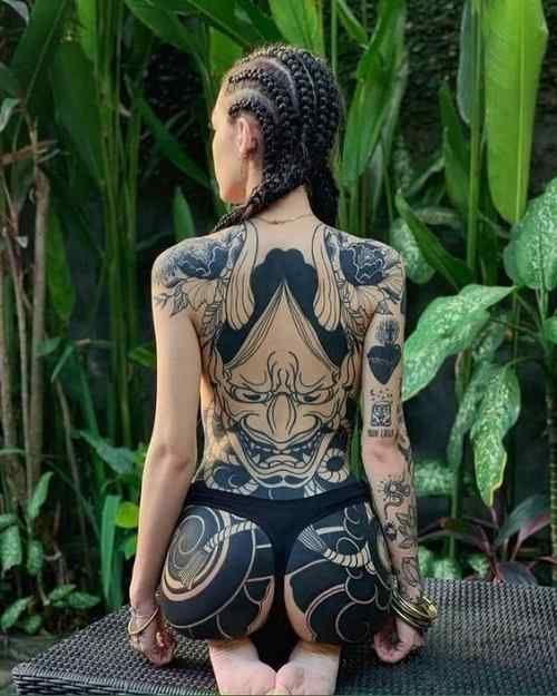 Mädchen mit Tätowierungen auf völlig Körper und etwas Liebe für rückseitige Tätowierungen zeigend