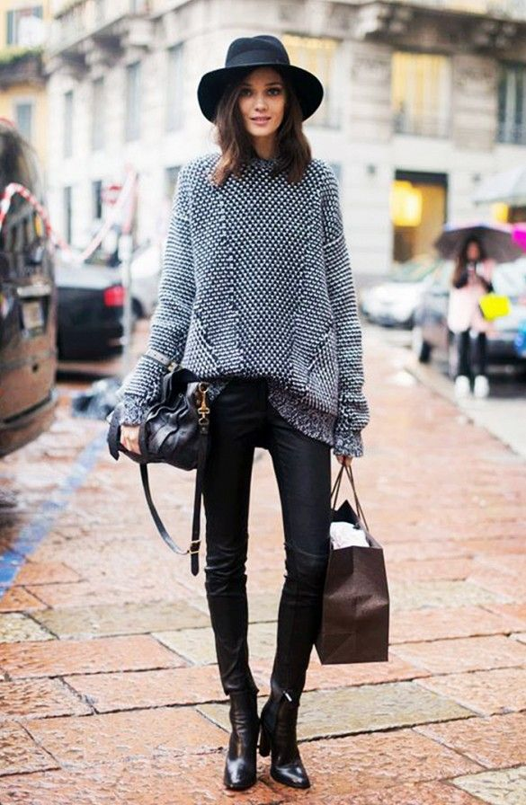 Black wide-brim hat, oversized knit sweater, black leather skinnies, and black ankle boots