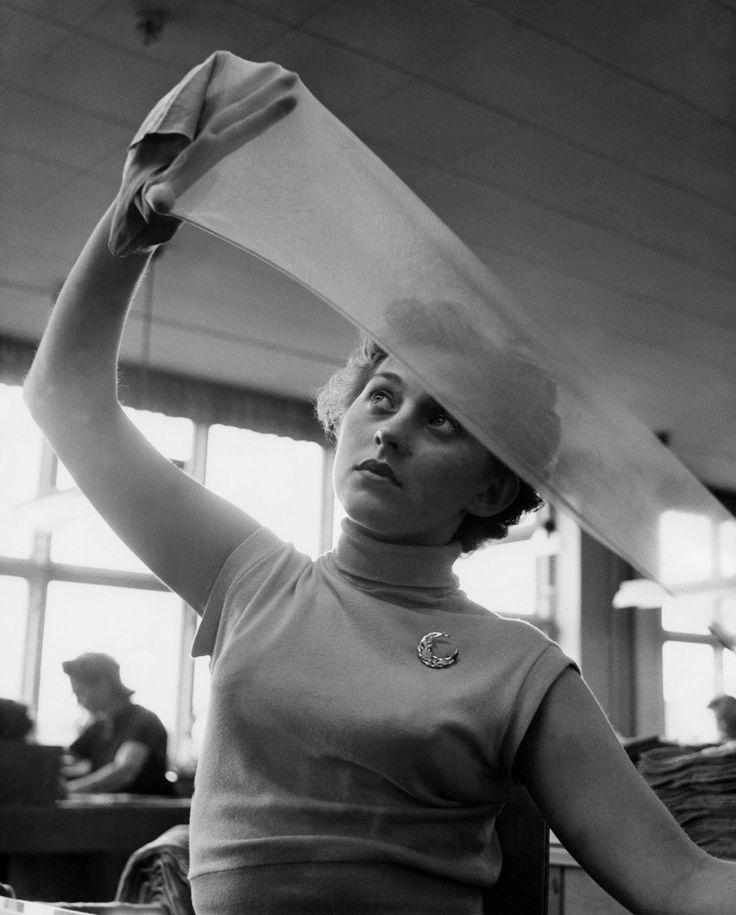 Kontroll av nylonstrumpor vid Malmö Strumpfabrik. En kvinna håller upp en strumpa mot ljuset för att undersöka kvaliteten. Foto: Erik Liljeroth, CC-BY.