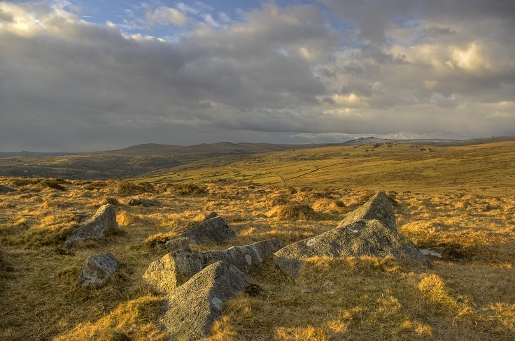 Golden hour evening sunlight, in early spring, bathes the hills above Merrivale and Walkhampton Common below. Snow dusts some of the higher ground in the distance.    Leedon Tor, Ingra Tor. King's Tor, Pew Tor, Heckwood Tor and Vixen Tor can be seen in the near distance.