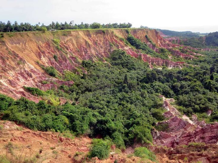 The colorful Diosso Gorge, 20 kilometers north of Pointe-Noire, Republic of Congo, features red rock cliffs up to 50 meters high.