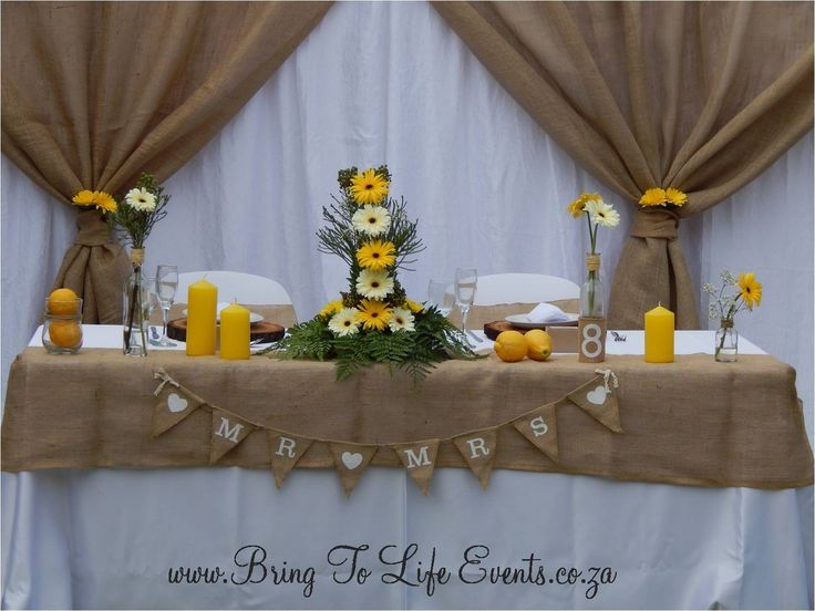 Rustic, garden wedding- Main table with hessian backdrop draping, hessian overlay, yellow and white gebera flower arrangement, lemons and yellow candles