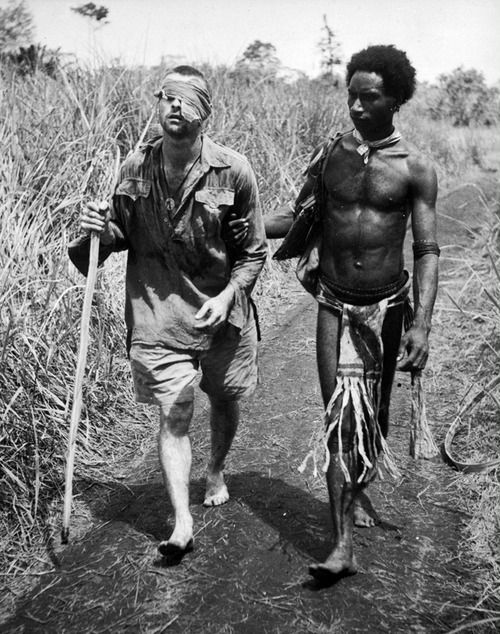 A blinded Australian soldier is guided to a field hospital away from the battlefront by a Papuan native. Buna, Christmas Day, 1942.