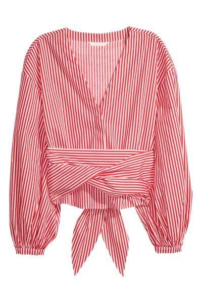 Een kortere blouse van geweven katoen met een V-hals met blinde sluiting voor en fors verlaagde schoudernaden. De blouse heeft wijde mouwen met een sluiting