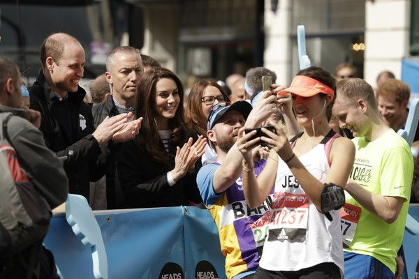 Kate Middleton Photos Photos - Runners stop to take selfies backdropped by Britain's Prince William, Duke of Cambridge and Catherine, Duchess of Cambridge cheering on runners at a Heads Together cheering point along the route of the 2017 London Marathon on April 23, 2017 in London, England. - The Duke