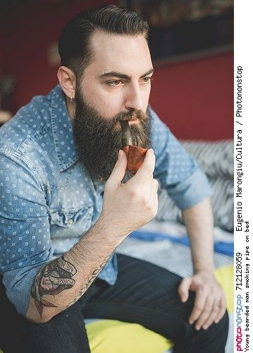 Young bearded man smoking pipe on bed -- Attitude Barbe Chemise Cheveux Cheveux Bruns Fumer Gros Plan Homme Image De   Personnage Phénomène Naturel Pipe Tabac Tatouage Vêtement