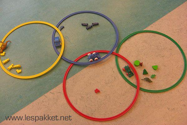 Olympische ringen  Een leuke opdracht met kleuren: leg 5 hoepels in de Olympische kleuren op de grond, middenin de kring. Vraag de kinderen nu voorwerpen in de klas te zoeken, die één van deze kleuren heeft. Het voorwerp wordt in de juiste hoepel gelegd. Ik heb deze opdracht ooit eens gedaan met 4 hoepels, en toen hadden we ineens een blauwe auto met gele wielen… Probleem? Nee hoor! Zo werkt een Venn-diagram, waarin je overeenkomsten en verschillen tussen voorwerpen kunt laten zien!