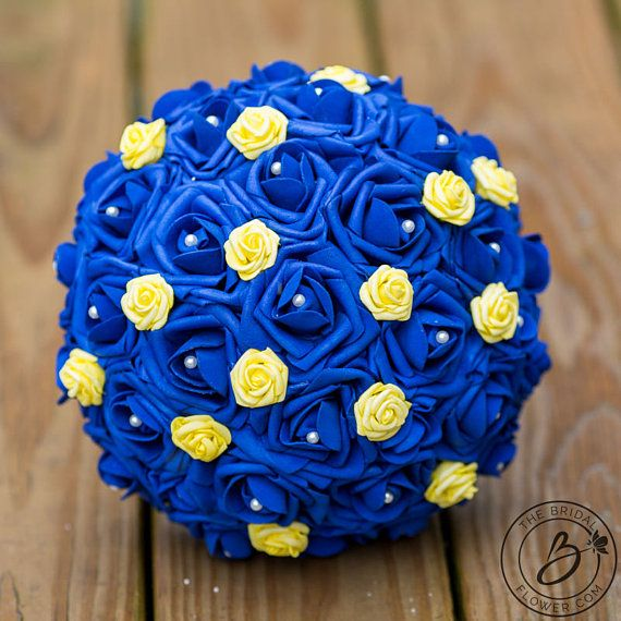 """""""Fit for a Princess Horizon Blue and Sunbeam Yellow Wedding Bouquet with Pearls  Be the belle of the ball with this gorgeous large royal blue and yellow wedding bouquet. This bouquet will take you back to your childhood imagining your dream princess wedding, only now it has been updated with elegance and attention to detail that will have all of your friends hoping you will say to them be my guest. Small sunbeam yellow rose really pop on the horizon blue background. Detailed pearl accents…"""