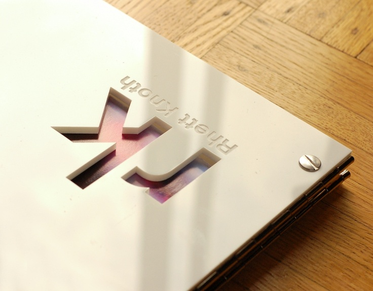 White acrylic screwpost portfolio with custom cut-out and engraving close up.