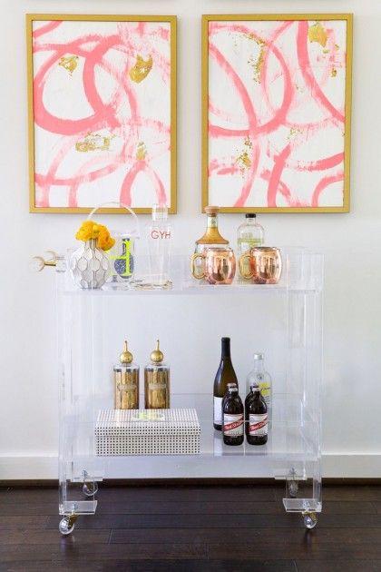 Feminine, lucite bar cart with pink artwork