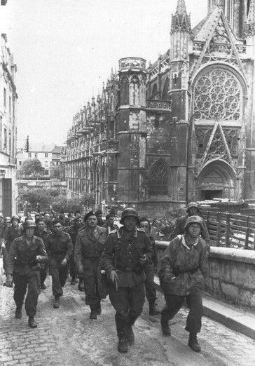 Caen, le matin du 6 juin 1944, des prisonniers canadiens du Régiment de la Chaudière, gravissent la rampe du château. En arrière plan l'église Saint- Pierre.