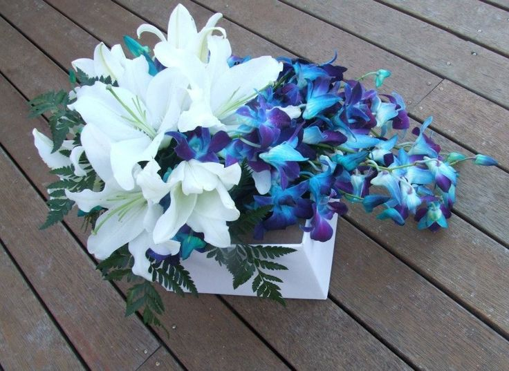 Blue - dyed Singapore Orchids, plus white oriental lilies and leather fern foliage.