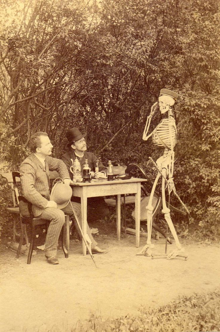 """German students, about 1890, posing with a skeleton wearing a student's cap. The picture is titled """"der Skatspiel mit freund Hein"""" - a game of cards with Death."""