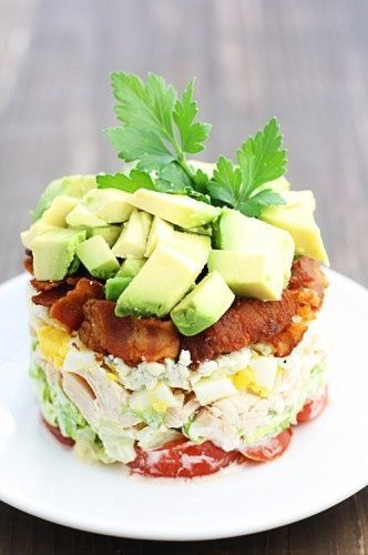 Stacked Cobb Salad Ingredients: 12 very large cherry tomatoes, sliced 1 1/2 cups chopped romaine lettuce 1 1/2 cups cooked, diced rotisserie chicken 4 hard-boiled eggs, diced 1/2 cup blue cheese crumbles 1 cup crumbled bacon 2 avocados, diced 1 cup good-quality mayonnaise 1 cup sour cream 4 oz blue cheese
