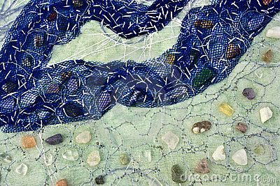 Detail of an abstract work of embroidery mostly in blue and green containing polished stones