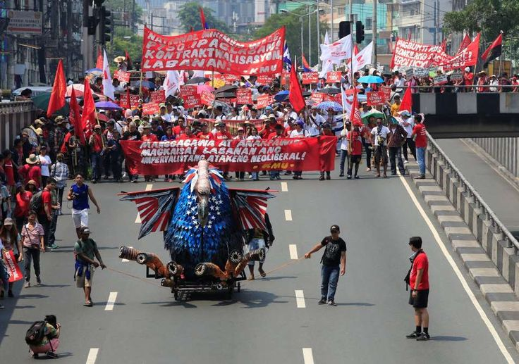 """May Day around the world  -  May 1, 2017:      An effigy of a vulture in US flag colors is pulled in front of various workers' groups marching during the annual Labor Day protest march in metro Manila, Philippines, on May 1, 2017. The banner reads: """"Workers unite against the imperialist attack of the neoliberal""""."""