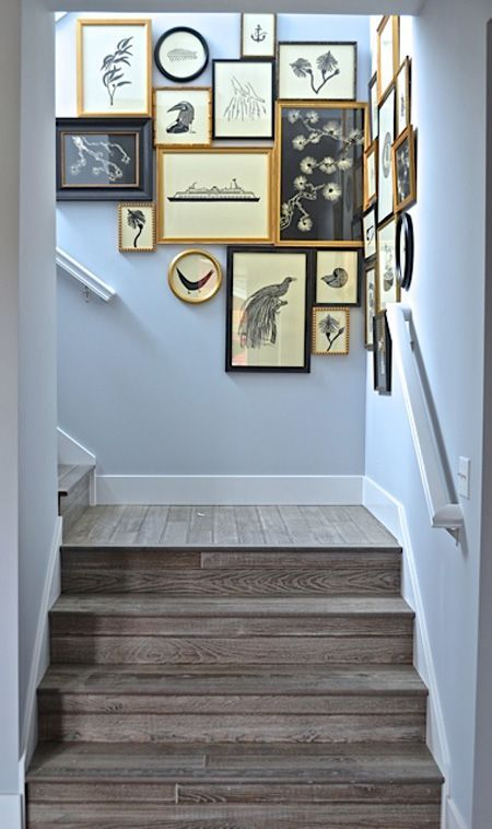 Gallery wall on pale blue staircase. Black and gold theme ties the pictures together