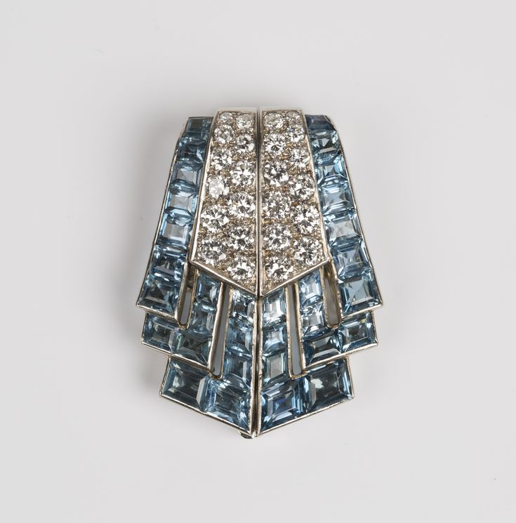 An Art Deco Boucheron 18ct white gold, diamond and aquamarine dress clip in a fanned design, mounted