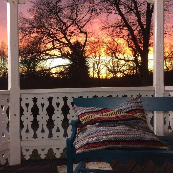 Kudde av trasmatta på bänk på veranda i solnedgång.