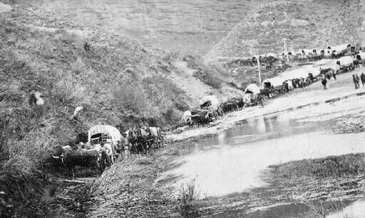 A pioneer wagon train winding down through Echo Canyon in 1868.