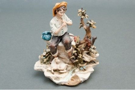 Superb Sculpture of Aci the Shepherd that plays for his Love Galatea in artistic Capodimonte porcelain masterfully carved with shepherd with flute sitting on rock and surrounded by trees, flowers and a beautiful  little lamb.  www.apoggi.com     Dimensions cm. 20x18