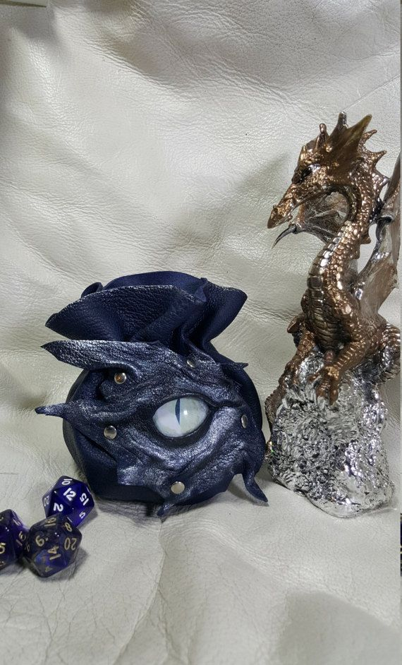 Handmade Leather Dice Bags With A Stunning White Dragons Eye .  Approx 4.5 high x 6 across with round bottom will Hold up to 35 dice..  Totally Handmade in Very Unusual one off soft Dark Blue leather with silver shimmer around the Eye and Silver Rivets.  Closes with Leather Thong and Spring Toggle.