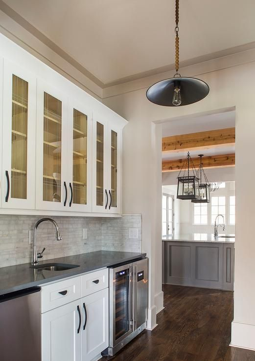 Cottage butler's pantry features glass front upper cabinets adorned with oil rubbed bronze pulls and lower cabinets topped with gray quartz fitted with a curved sink and gooseneck faucet flanked by a stainless steel mini fridge to the left and side by side wine coolers to the right illuminated by a vintage rope barn pendant.