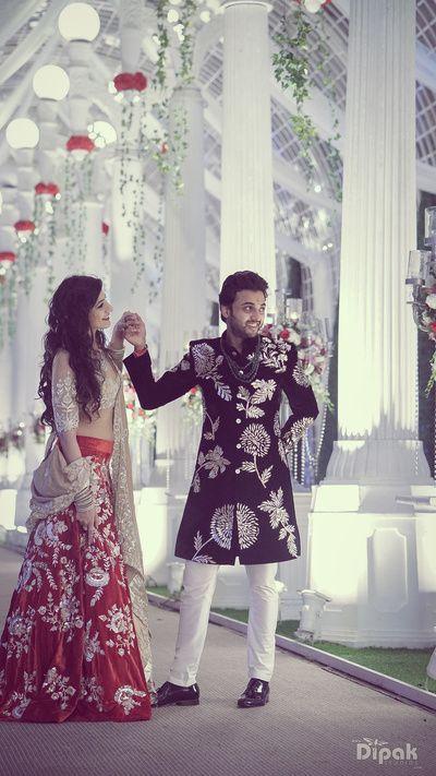 Bridal Lehengas - Red Velvet Lehenga and Wine Sherwani | WedMeGood | Matching Outfits with the Groom in a Wine Sherwani and Silver Embroidery and the Bride in a Red Velvet Lehenga with a Beige Blouse #wedmegood #indianwedding #indianbride #couple #velvet #lehenga #bridal