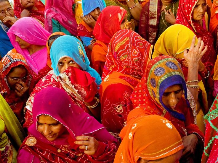 Women in bright saris crowd together as they walk in a bridal procession in Mandawa, Rajasthan. Rajasthan is the largest state in India.