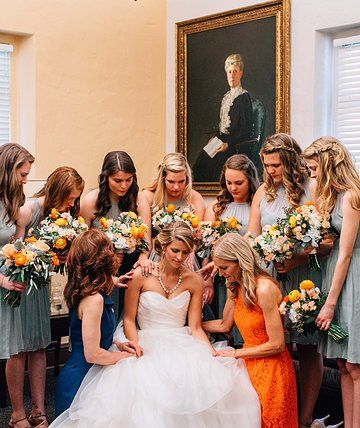 a quiet moment for the bride to be with the bridesmaids and mothers. bouquets of cream, peach and orange complete the circle of prayer.