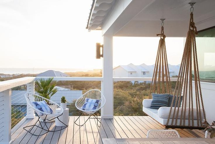 Chic covered second floor balcony is fitted with a rope swing bed adorned with…