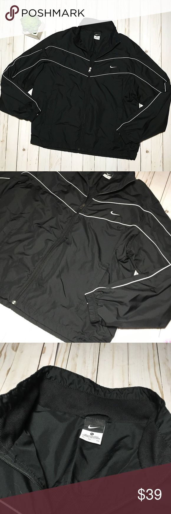 Vintage Nike Black Windbreaker Pre-owned black Nike windbreaker jacket with white Nike tick & white lines. In excellent condition- no holes or stains. Size XL but please see measurements below. Has place to thread headphone wire through on the inside.  APPROX. MEASUREMENTS (LAYING FLAT): bust: 20.5in length: 28in sleeve length: 26in Nike Jackets & Coats Windbreakers