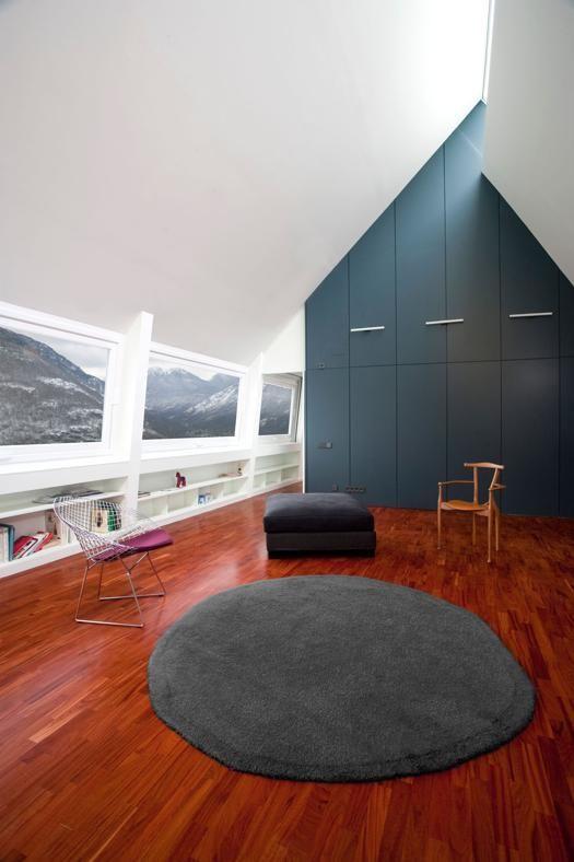 Baita 2.0 Funzionale, la parte superiore dell'abitazione sfrutta l'altezza eccezionale del soffitto con un guardaroba disegnato dagli architetti Eduardo Cadaval & Clara Solà-Morales. Su disegno anche la fila di scaffali che corre sotto le finestre.