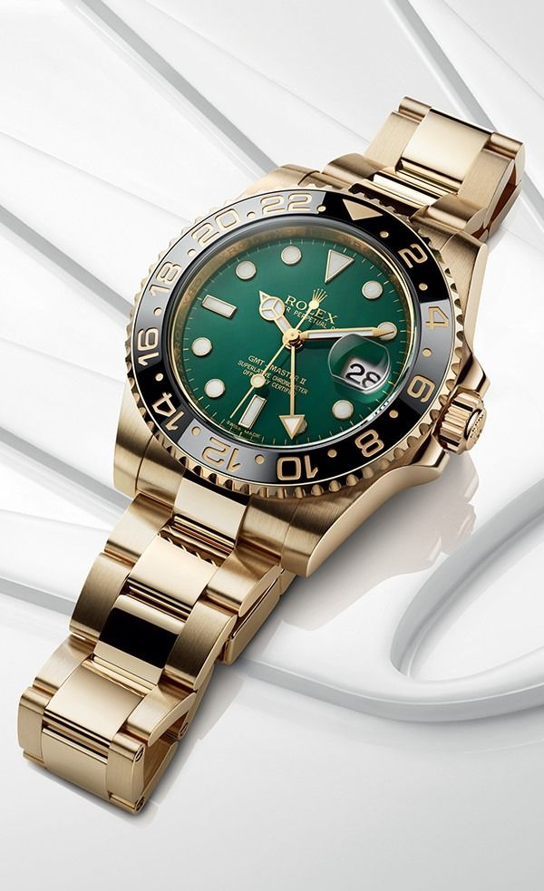 The distinctive face of a Rolex GMT-Master II in 18ct yellow gold with a green dial and a black Cerachrom bezel in ceramic.